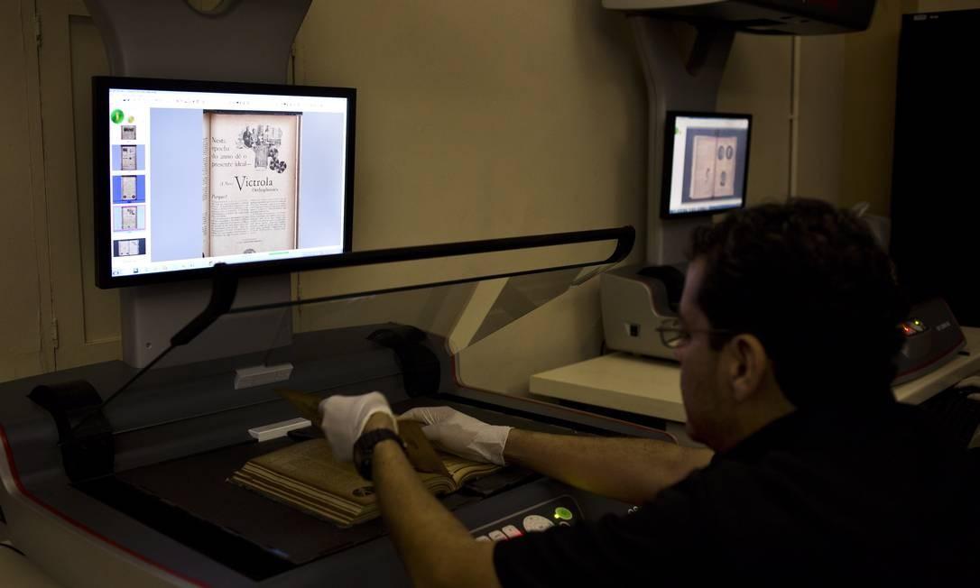 Tecnologia. Funcionário da Biblioteca Nacional digitaliza edição rara a partir do original Foto: Paula Giolito / O Globo