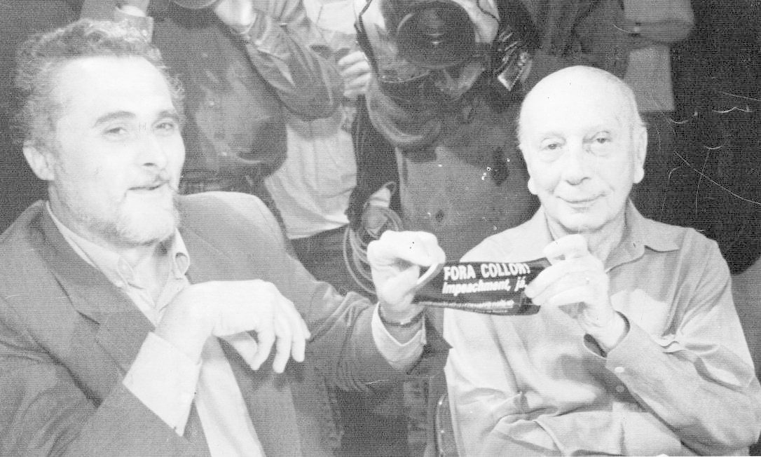"""(27/09/1992) Ulysses Guimarães e José Genoino seguram um adesivo """"Fora Collor"""" em reunião pró-impeachment Foto: Arquivo O Globo"""