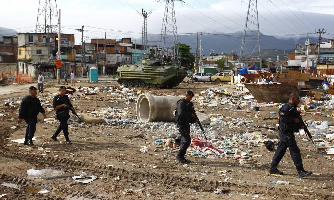 Durante a ocupação, policiais caminham em terreno baldio em Manguinhos onde há lixo Foto: Pablo Jacob / O Globo