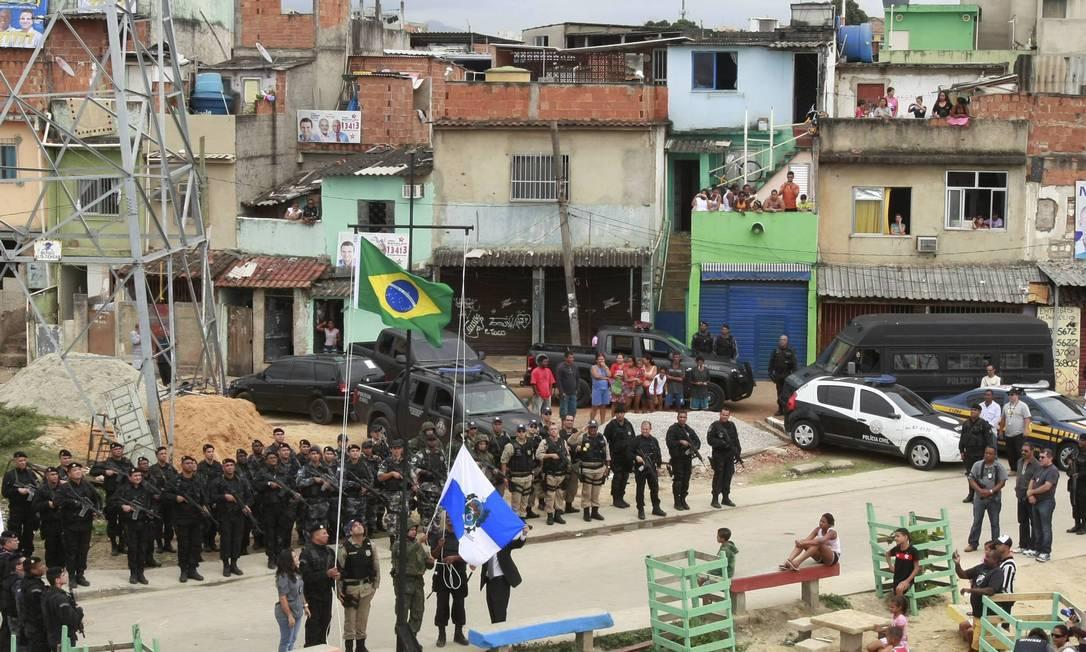 Bandeiras do Brasil e do governo do estado são hasteadas em Manguinhos Foto: Fabiano Rocha / Extra / O Globo