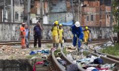 Garis da Comlurb retiram lixo e sujeira da linha do trem no Jacarezinho Foto: Márcia Foletto / O Globo