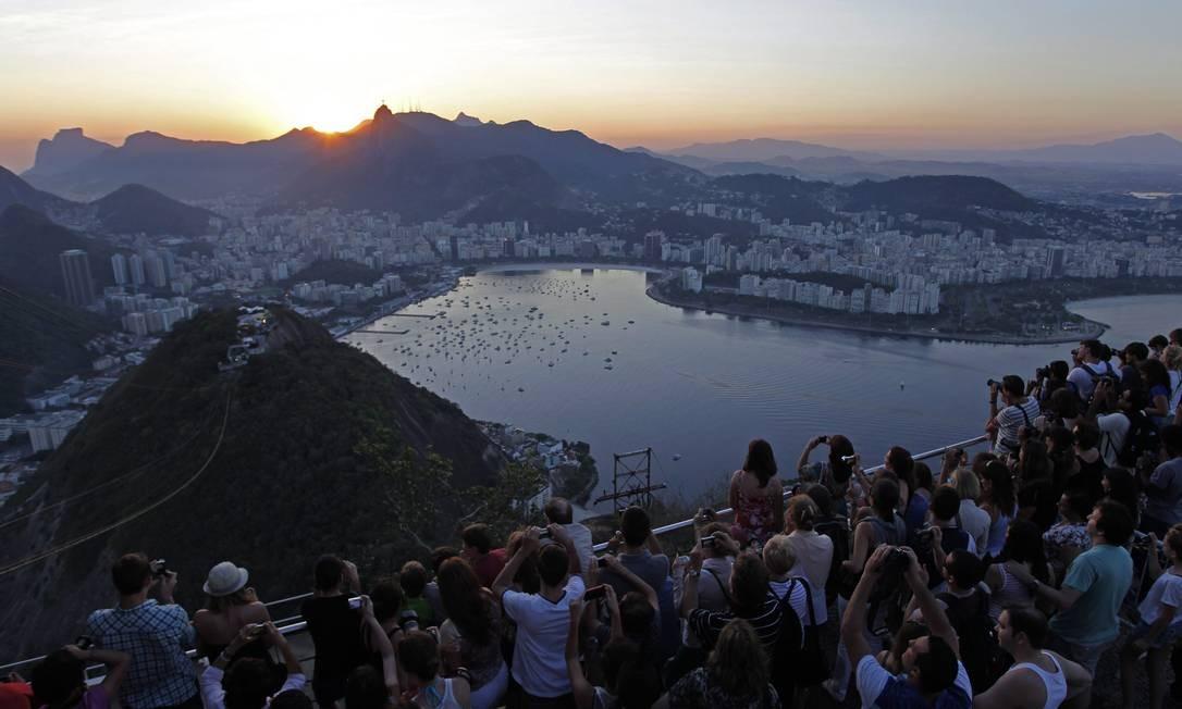Turistas disputam espaço no Morro da Urca para fotografar o pôr do sol Foto: Custodio Coimbra / O Globo