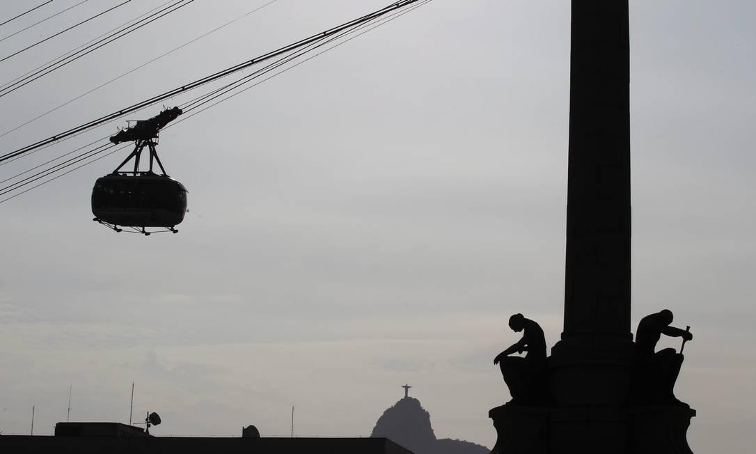 O bondinho desliza nos céus da Urca protegido pelo Cristo Redentor, outro ícone da cidade Foto: Custodio Coimbra / O Globo
