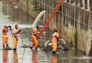 Mãos à obra. Garis da Comlurb limpam um Rio Jacaré tomado de sujeira Foto: Gabriel de Paiva / O Globo