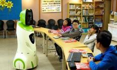 Crianças usam um robô em escola coreana Foto: AFP