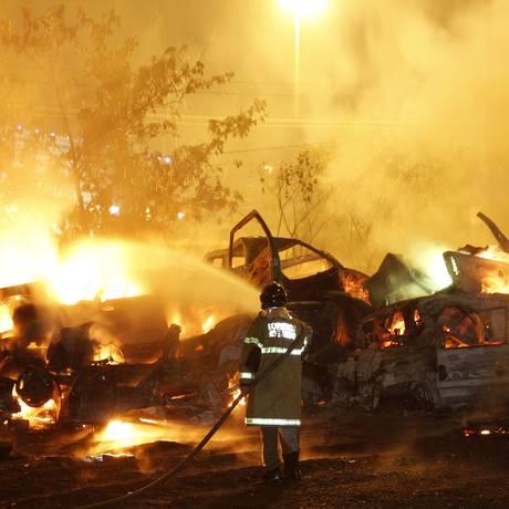 Bombeiro combate as chamas do incêndio no depósito de veículos da Polícia Civil, no Trevo das Margaridas Foto: Fernando Quevedo / O Globo