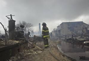 Bombeiro trabalha no rescaldo em Breezy Point, no Queens: pelo menos 80 casas destruídas Foto: Reuters