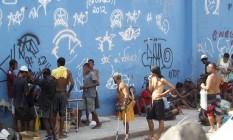 A banca do crack. Viciados, um deles até de muletas, fazem fila para comprar a droga em avenida que dá acesso à Ilha pela Avenida Brasil Foto: Marcelo Carnaval / O Globo