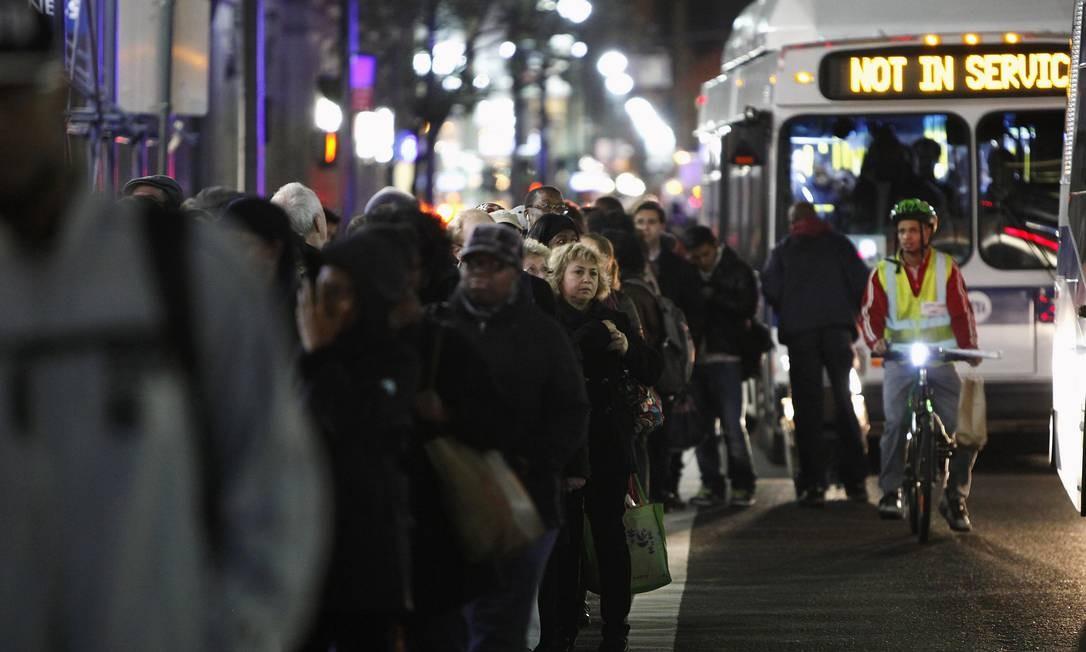 Pessoas na fila para pegar ônibus em Manhattan, em Nova York Foto: REUTERS/Carlo Allegri