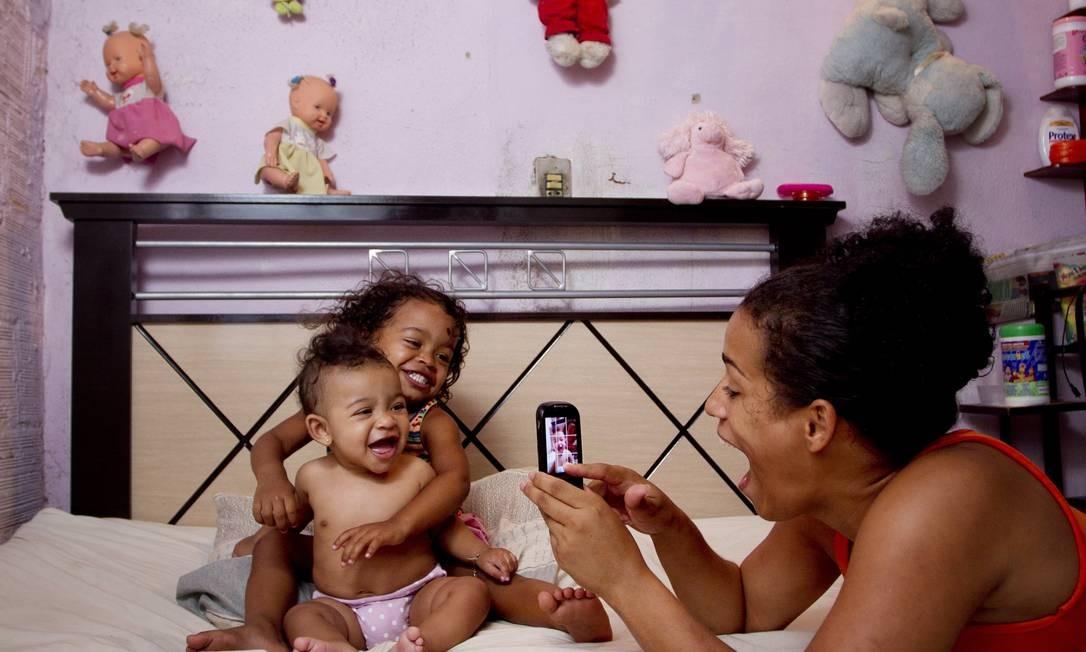 Sem certidão de nascimento, Camila fotografa as duas filhas, Camille, de 2 anos, e Sofia, de 5 meses, também sem registro oficial, em casa minúscula no Gamboa Foto: Márcia Foletto / O Globo