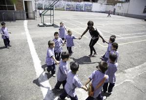 Intercâmbio cultural. Professora brasileira que participou do projeto Escola de Leitores brinca de roda com alunos da escola pública Benjamín Herrera, em Medellín Foto: Paul Smith/Instituto C&A