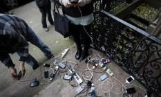 Morador disponibiliza energia de sua própria casa para que vizinhos possam recarregar celulares: gasolina, alimentos, água e energia são produtos mais visados após passagem de tempestade Sandy Foto: AFP