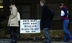 Pleito poliglota. Em Boston, Massachusetts, eleitores esperam na fila para votar, diante de uma placa com dizeres em vários idiomas que indica o caminho da seção eleitoral Foto: Mike Segar/Reuters