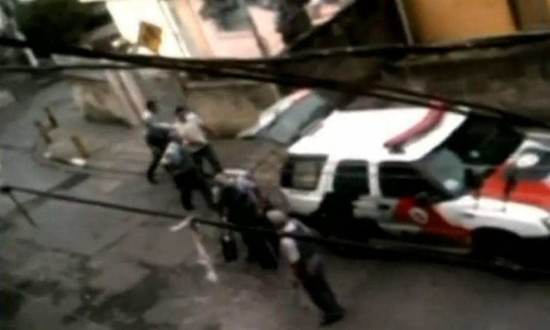 Vizinho flagra servente sendo levado por policiais Foto: Reprodução TV