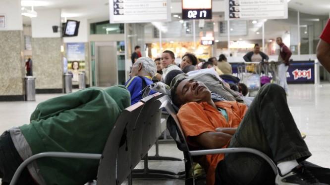 Cochilo desconfortável. Espremido num banco, o pedreiro Mauro César Souza dorme à espera do ônibus para o Piauí: passageiros improvisam de madrugada na rodoviária Foto: Fernando Quevedo / O Globo