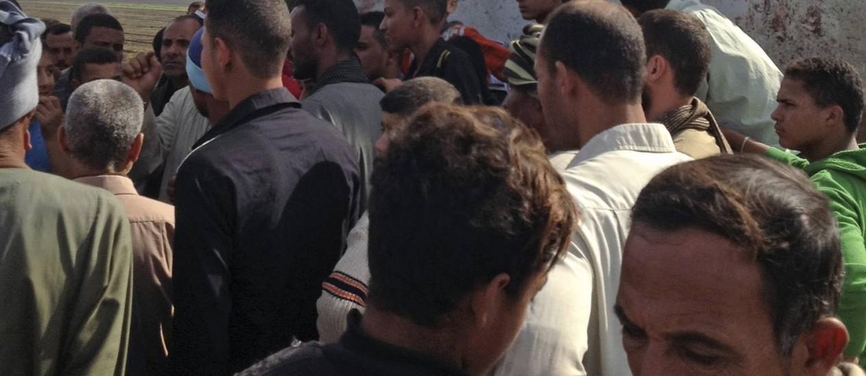 Egípcios se reúnem no local do acidente, perto de Assiut: país tem histórico de acidentes em estradas e linhas férreas Foto: Mamdouh Thabet / AP