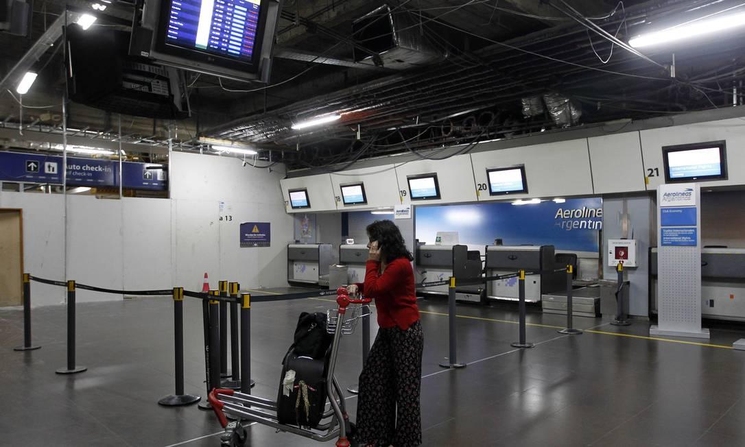 Ilhada no Aeroporto de Buenos Aires, passageira aguarda perto do balcão da Aerolíneas Argentinas Foto: ENRIQUE MARCARIAN / REUTERS