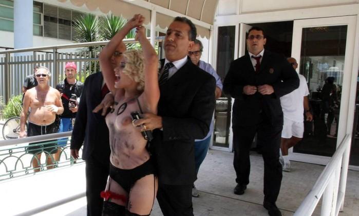 Segurança leva uma das manifestantes para fora do hotel Guilherme Pinto / Extra