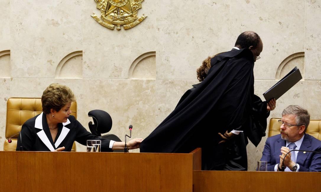 A presidente Dilma Rousseff solta a capa preta do ministro Joaquim Barbosa que, ao levantar para discursar, ficou presa na cadeira especial durante a posse na presidencia do STF Foto: O Globo / Gustavo Miranda