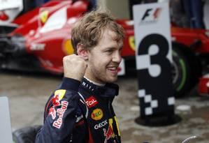 Vettel comemora a conquista do título, próximo a um carro da Ferrari, após o GP do Brasil Foto: Silvia Izquierdo / AP