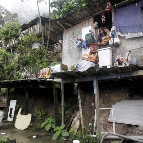 Perigo. Jefferson com a filha num dos barracos de madeira do Dona Marta: à espera de realocação desde 2008 Foto: Custódio Coimbra / O Globo