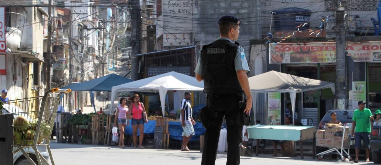Medo de volta . PM da UPP da Vila Cruzeiro observa o movimento na favela Foto: Domingos Peixoto
