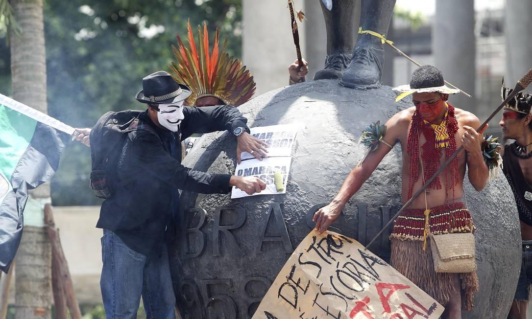 Manifestantes colam cartazes de protesto contra a demolição do Complexo do Maracanã e da Escola Municipal Friedenreich na Estátua do Belini Foto: Alexandre Cassiano / O Globo