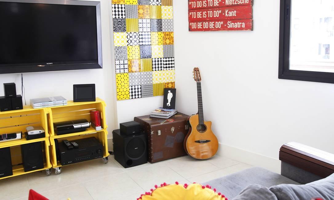 Na sala, rack e parede de azulejos feito pela moradora Foto: Ana Branco