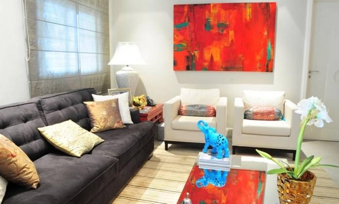 No projeto do arquiteto Aurélio Begliomini, o quadro vermelho e o elefante de porcelana azul colorem o ambiente que tem o sofá preto como peça principal. Poltronas brancas iluminam a decoração Divulgação