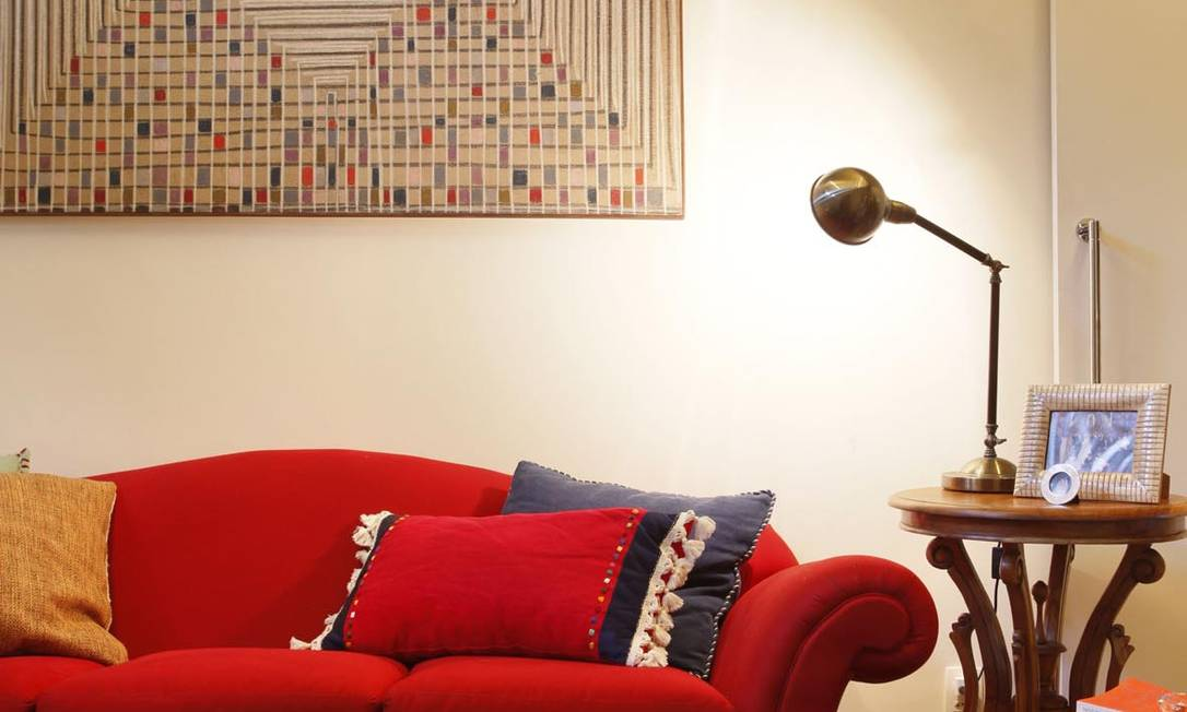 No projeto da Escala Arquitetura, o sofá vermelho cria um clima aconchegante e rouba a cena, complementado pela combinação de almofadas com detalhes em azul Divulgação