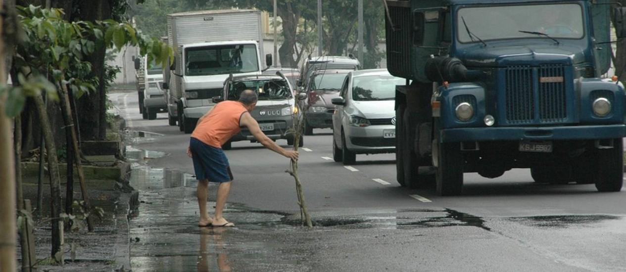Morador tenta alertar motoristas sobre o perigo causado pelo buraco na Avenida Alberico Diniz, na Zona Oeste Foto: Foto do leitor Paulo Roberto de Freitas/ Eu-Repórter