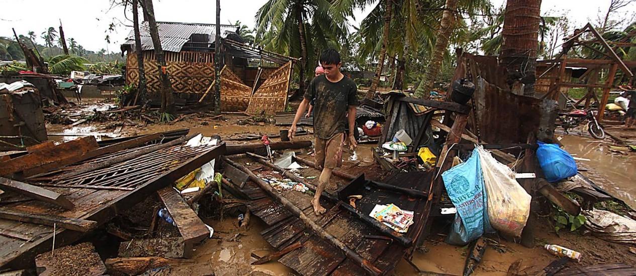 Menino anda pelos escombros de casas destruídas pelo tufão Bopha nas Filipinas Foto: AFP/KARLOS MANLUPIG