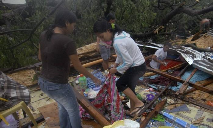 Jovens tentam recolher pertences em destroços de uma casa na cidade Oro, no sul do país Reuters/STRINGER