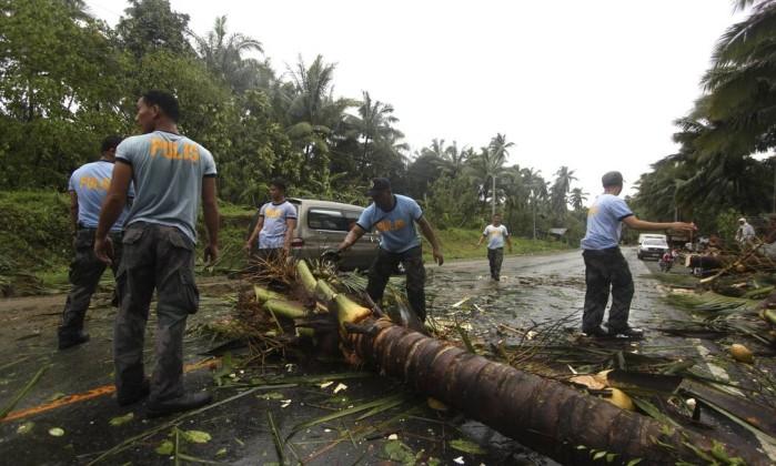 Agentes da polícia nacional tentam remover uma árvore que bloqueia um importante via em Compostela Valley, a província mais atingida AP/Karlos Manlupig