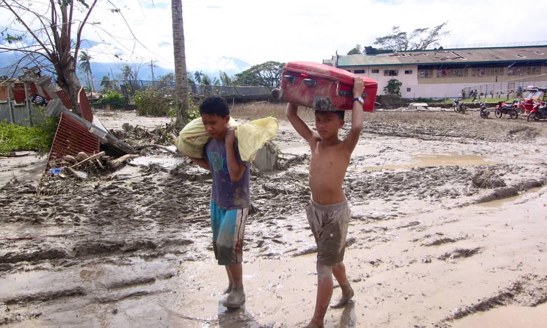 Dois jovens carregam o que sobrou de seus pertences após a passagem do tufão em Compostela Valley AFP PHOTO / Karlos Manlupig