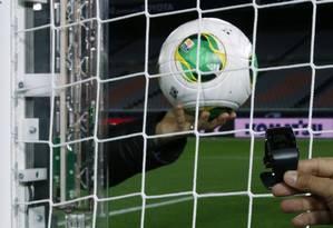 O novo sistema implantado na trave e a bola com o chip que avisa quando é gol Foto: Toru Hanai / Reuters