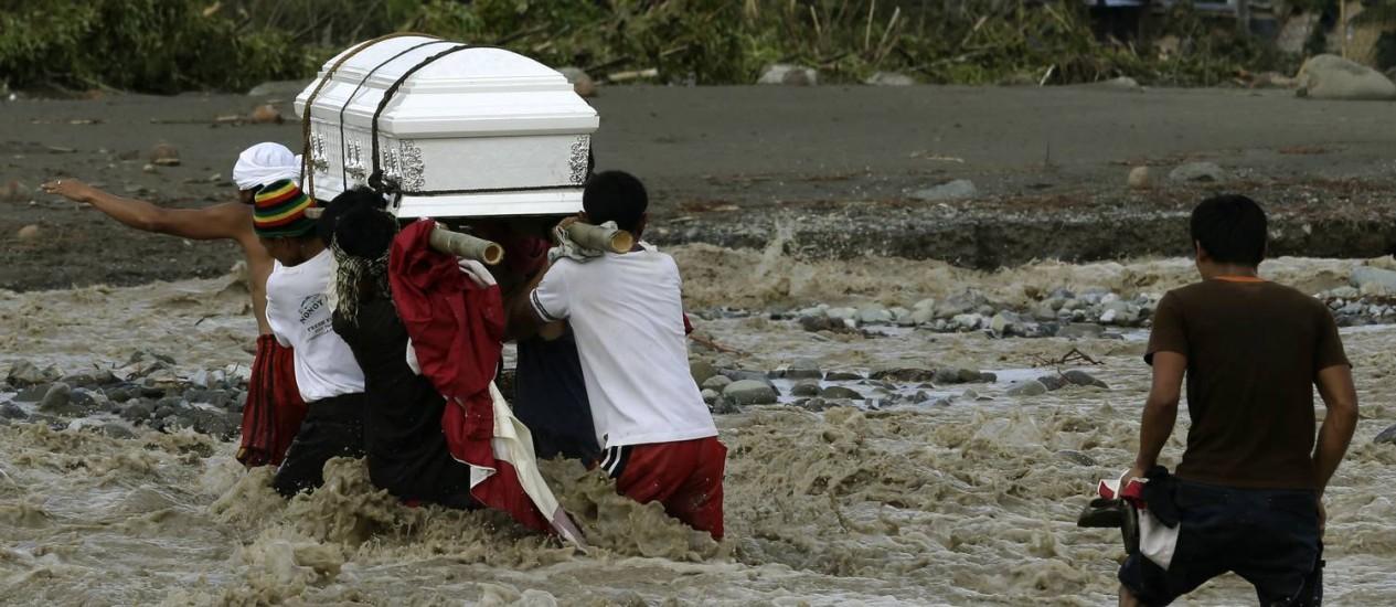 Filipinos tentam atravessam um rio com um caixão de uma vítima do tufão Bopha em New Bataan, no Compostela Valley Foto: AP