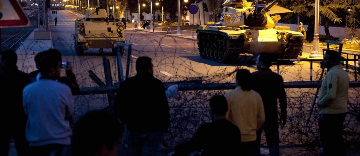Tanques do Exército egípcio observam manifestantes do outro lado da cerca de isolamento do palácio presidencial Foto: AP/Nasser Nasser