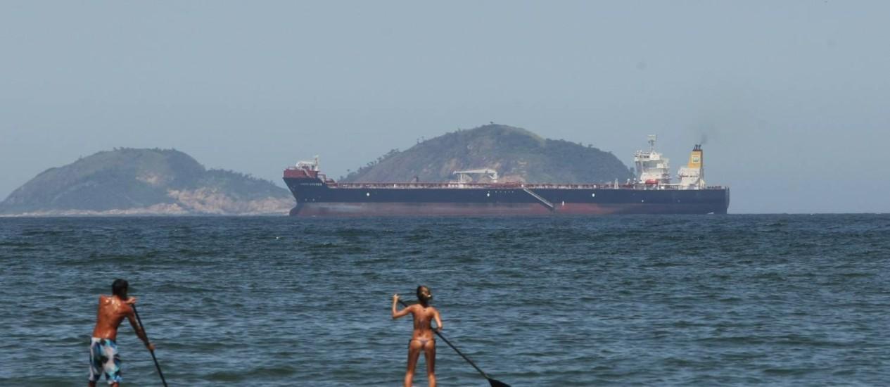 Poluição visual. Da Praia de Copacabana, surfistas avistam uma das grandes embarcações que passam em frente à orla da Zona Sul , impedindo a visão das Ilhas Cagarras Foto: Eduardo Naddar/06-12-2012 / O Globo