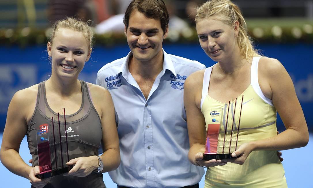 Anfitrião do evento, o suíço Roger Federer posa entre as musas do tênis feminino após a partida. A russa Maria Sharapova (à direita) derrotou a dinamarquesa Caroline Wozniacki por 2 sets a 0 Andre Penner / AP