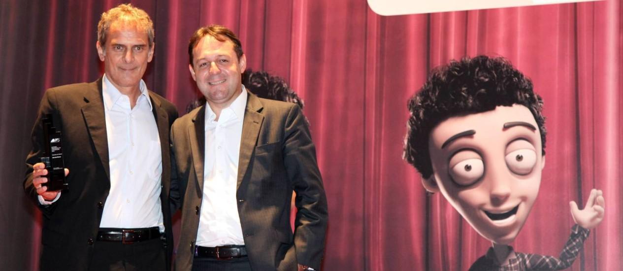 O diretor-geral da Infoglobo, Marcello Moraes, após receber troféu de Claudio Paim, diretor da ABP Foto: Fabio Rossi / Agência O Globo