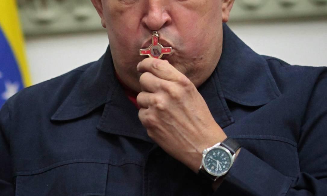 Presidente Hugo Chávez beija uma cruz durante pronunciamento do Palácio Miraflores, em Caracas, sobre necessidade de nova cirurgia contra câncer Foto: Marcelo Garcia / AP
