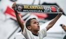 Em São Paulo, o pequeno torcedor corintiano exibe com o orgulho a faixa de bicampeão mundial Foto: Yasuyoshi CHIBA / AFP
