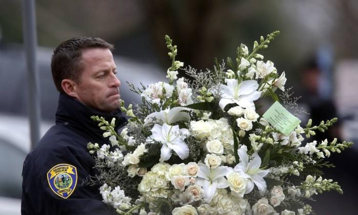 Um policial local levou flores, em homenagem ao menino Jason DeCrow / AP