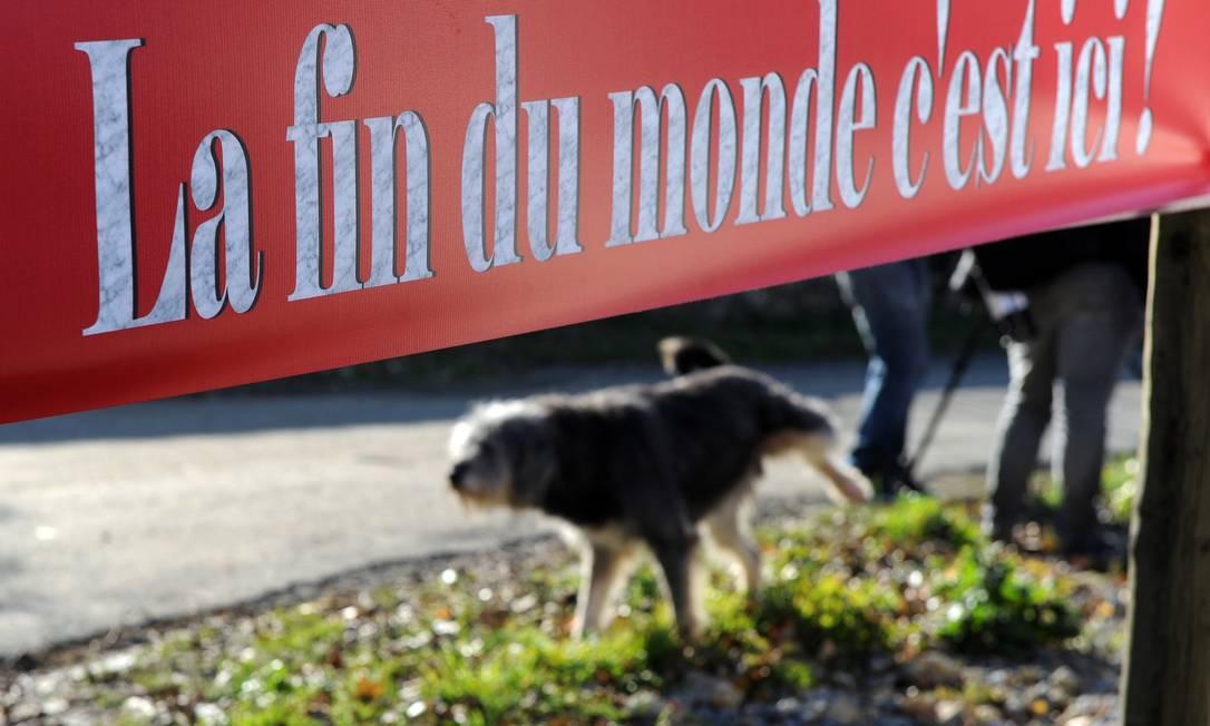 """Mesmo assim, a ideia está divertindo muita gente. Em um restaurante na comuna francesa de Bugarach, uma placa informa: """"O fim do mundo é aqui!"""" Eric Cabanis / AFP"""