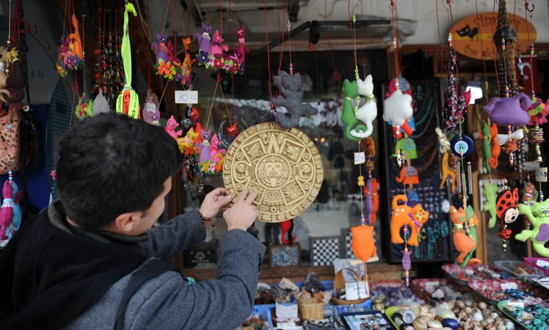 Na aldeia, produtos alusivos ao apocalipse maia servem de souvenires. Na foto, um turista observa um símbolo maia BULENT KILIC / AFP