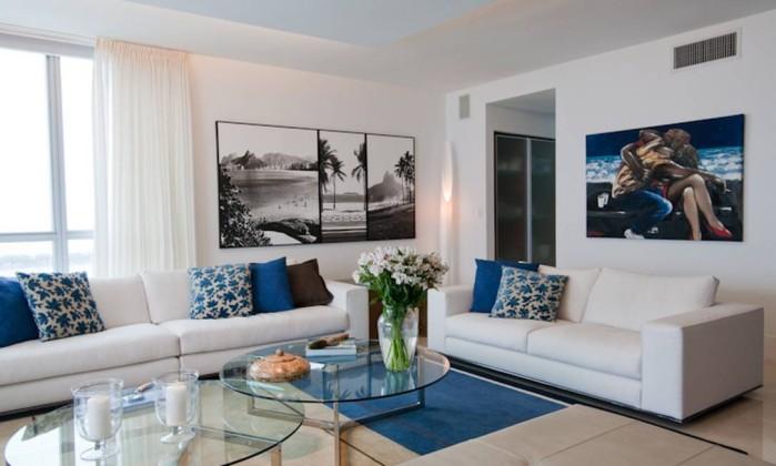 Almofadas e tapete em tons de azul e marrom levam o olhar do leitor para o conjunto de sofás branco, em projeto da arquiteta Andréa Chicharo Divulgação