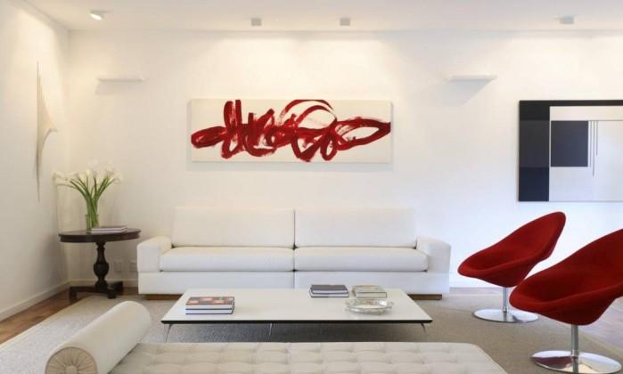 Nesta sala assinada pelo trio de arquitetas Roberta Moura, Paula Faria e Luciana Mambrini, o sofá faz parte da elegante combinação de branco e vermelho Divulgação