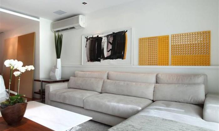 Sofá branco com chaise é a estrela do ambiente em projeto do escritório Yamagata, que ganha cor através das obras de arte Divulgação