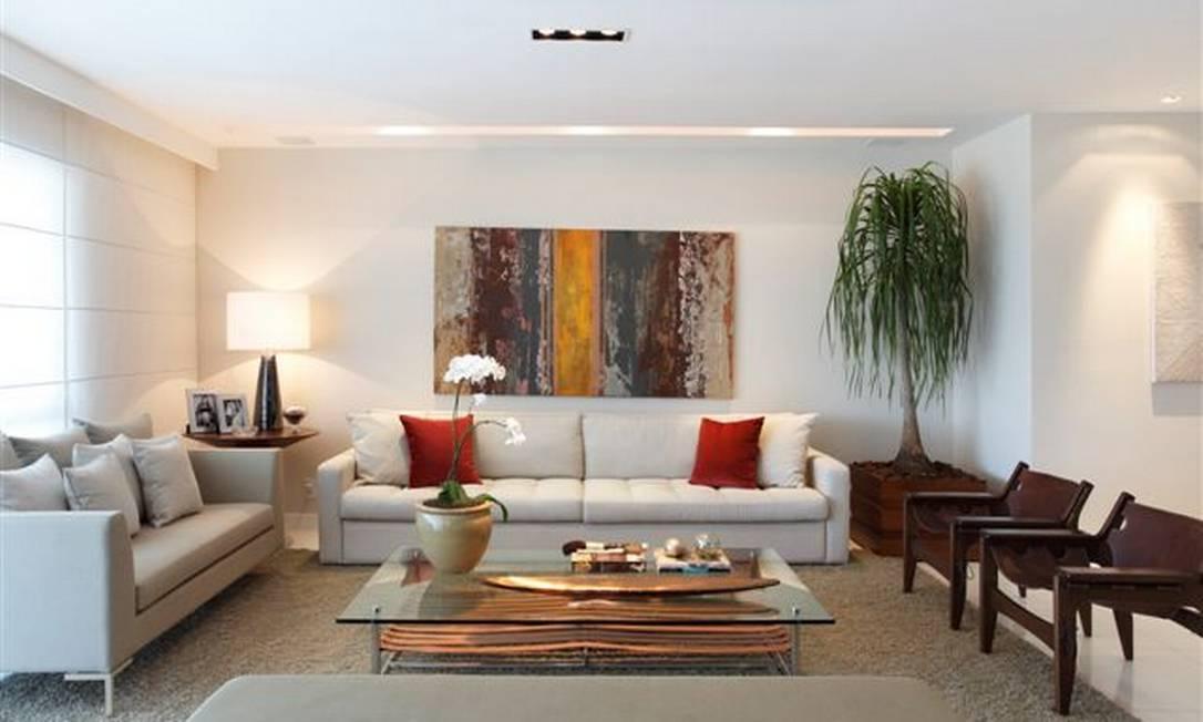 Conforto é a palavra de ordem no projeto da arquiteta Patrícia Fiúza, que também usa cores alegres como o laranja e o vermelho para destacar o sofá branco desta sala